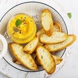 Ένα υγιές πρόχειρο φαγητό στο πικ-νίκ: juicy πικάντικη εμβύθιση καρότων με τις τραγανές φέτες ψωμιού στη σχάρα σε ένα ελαφρύ υπόβ Στοκ Φωτογραφίες