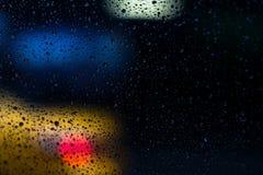 Ένα υγρό ουράνιο τόξο κατά τη διάρκεια μιας βροχερής ημέρας με το θολωμένο αμάξι ταξί στο υπόβαθρο στοκ εικόνες