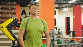 Ένα υπέρβαρο άτομο ανυψώνει ένα ez barbell στεμένος στη γυμναστική Άσκηση για τους δικέφαλους μυς E r φιλμ μικρού μήκους