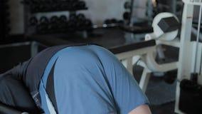 Ένα υπέρβαρο ενήλικο άτομο εκτελεί hyperextension σε μια γυμναστική φιλμ μικρού μήκους
