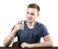 Ένα λυπημένο άτομο νεολαίας πίνει ένα ποτήρι του νερού, που απομονώνεται σε ένα άσπρο υπόβαθρο Ο ενοχλημένος τύπος παίρνει τα χάπ Στοκ Εικόνα