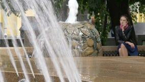 Ένα λυπημένο όμορφο κορίτσι κάθεται σε ένα πάρκο, κοντά σε μια πηγή Κακά ειδήσεις, απόγνωση και απόθεμα βίντεο