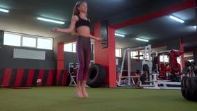 Ένα φίλαθλο κορίτσι πηδά το σχοινί στη γυμναστική Το όμορφο κορίτσι στην αθλητική λέσχη κάνει το διαφορετικό είδος ασκήσεων φιλμ μικρού μήκους