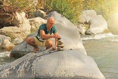 Ένα φαλακρό άτομο χτίζει έναν πύργο των πετρών στη φύση, ενάντια στο β στοκ φωτογραφία με δικαίωμα ελεύθερης χρήσης