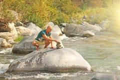 Ένα φαλακρό άτομο χτίζει έναν πύργο των πετρών στη φύση, ενάντια στο β στοκ εικόνες