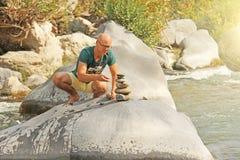 Ένα φαλακρό άτομο χτίζει έναν πύργο των πετρών στη φύση, ενάντια στο β στοκ φωτογραφίες