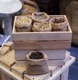 Ένα φασόλι καφέ σε ένα εμπορευματοκιβώτιο και με ψημένος και ακατέργαστος Αντιπροσωπεύστε έναν φρέσκο και μια μυρωδιά του καφέ Στοκ Εικόνες