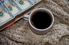 Ένα φλιτζάνι του καφέ, δολάρια και ένα βιβλίο σε ένα θερμό μαντίλι στοκ εικόνα