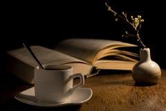 Ένα φλιτζάνι του καφέ και ένα βιβλίο στον πίνακα Στοκ εικόνα με δικαίωμα ελεύθερης χρήσης