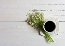 Ένα φλιτζάνι του καφέ και μια ανθοδέσμη του κρίνου της κοιλάδας ανθίζουν σε έναν άσπρο ξύλινο πίνακα, τοπ άποψη Στοκ Εικόνα
