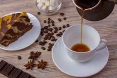 Ένα φλιτζάνι του καφέ και ένα νόστιμο κέικ σε ένα πιατάκι Φραγμός σοκολάτας, φασόλια καφέ, ένα κύπελλο με τους κύβους ζάχαρης, κα Στοκ φωτογραφία με δικαίωμα ελεύθερης χρήσης