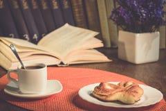 Ένα φλιτζάνι του καφέ και ένα πιάτο με ένα κουλούρι στον πίνακα Στοκ εικόνες με δικαίωμα ελεύθερης χρήσης