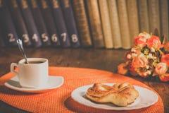 Ένα φλιτζάνι του καφέ και ένα πιάτο με τις ζύμες Στοκ Εικόνα