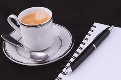 Ένα φλιτζάνι του καφέ με ένα σημειωματάριο Στοκ Εικόνες