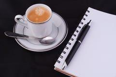 Ένα φλιτζάνι του καφέ με ένα σημειωματάριο Στοκ φωτογραφίες με δικαίωμα ελεύθερης χρήσης