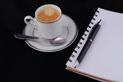 Ένα φλιτζάνι του καφέ με ένα σημειωματάριο Στοκ φωτογραφία με δικαίωμα ελεύθερης χρήσης