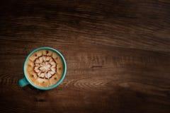 Ένα φλιτζάνι του καφέ με ένα σχέδιο τέχνης στην κορυφή του στοκ εικόνες