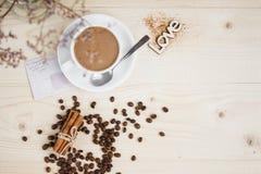 Ένα φλιτζάνι του καφέ με τα φασόλια κανέλας και καφέ σε έναν ξύλινο πίνακα Στοκ εικόνες με δικαίωμα ελεύθερης χρήσης