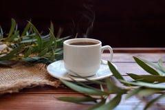 Ένα φλιτζάνι του καφέ με τον ευκάλυπτο διακλαδίζεται σε ένα ξύλινο υπόβαθρο στοκ εικόνα