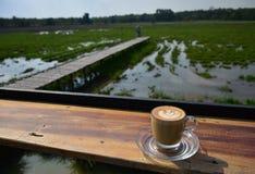 Ένα φλιτζάνι του καφέ με το σχέδιο τέχνης κατά την άποψη πρωινού στοκ φωτογραφία με δικαίωμα ελεύθερης χρήσης