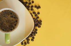 Ένα φλιτζάνι του καφέ πέρα από τα κίτρινα φασόλια εδάφους και καφέ στοκ εικόνα με δικαίωμα ελεύθερης χρήσης