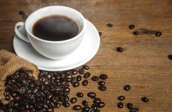 Ένα φλιτζάνι του καφέ που έχει τον καπνό και τα φασόλια στον ξύλινο πίνακα το espresso μπορεί να χρησιμοποιήσει για το σχέδιο δια Στοκ Εικόνα