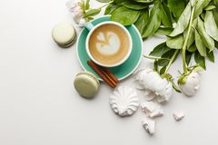 Ένα φλιτζάνι του καφέ σε έναν άσπρο πίνακα με τα peonies, τα γλυκά και τα φρούτα στοκ φωτογραφία με δικαίωμα ελεύθερης χρήσης