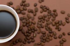 Ένα φλιτζάνι του καφέ σε ένα καφετί υπόβαθρο Στοκ Εικόνες