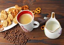 Ένα φλιτζάνι του καφέ, σιτάρια του καφέ και μπισκότα σε έναν ξύλινο πίνακα στοκ εικόνα