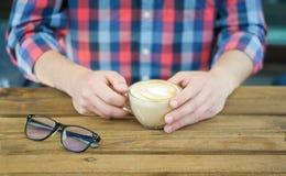 Ένα φλιτζάνι του καφέ στα χέρια ατόμων ` s στοκ φωτογραφία με δικαίωμα ελεύθερης χρήσης