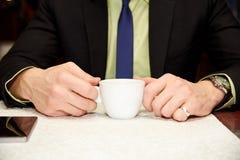 Ένα φλιτζάνι του καφέ στα χέρια ενός μοντέρνου επιχειρηματία στοκ εικόνες