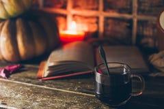 Ένα φλιτζάνι του καφέ στην άνετη αγροτική ατμόσφαιρα φθινοπώρου με τα κεριά και ένα βιβλίο στοκ φωτογραφία