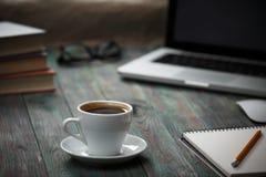 Ένα φλιτζάνι του καφέ στον εργασιακό χώρο σε έναν ξύλινο πίνακα Στοκ Εικόνα