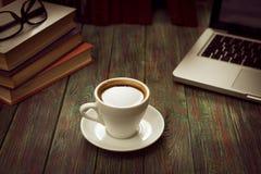 Ένα φλιτζάνι του καφέ στον εργασιακό χώρο σε έναν ξύλινο πίνακα Στοκ εικόνα με δικαίωμα ελεύθερης χρήσης