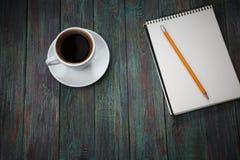 Ένα φλιτζάνι του καφέ στον εργασιακό χώρο σε έναν ξύλινο πίνακα Στοκ Εικόνες