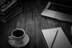 Ένα φλιτζάνι του καφέ στον εργασιακό χώρο σε έναν ξύλινο πίνακα Στοκ εικόνες με δικαίωμα ελεύθερης χρήσης
