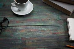 Ένα φλιτζάνι του καφέ στον εργασιακό χώρο σε έναν ξύλινο πίνακα Στοκ Φωτογραφία