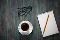 Ένα φλιτζάνι του καφέ στον εργασιακό χώρο σε έναν ξύλινο πίνακα Στοκ φωτογραφία με δικαίωμα ελεύθερης χρήσης