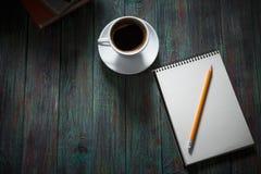 Ένα φλιτζάνι του καφέ στον εργασιακό χώρο σε έναν ξύλινο πίνακα Στοκ Φωτογραφίες