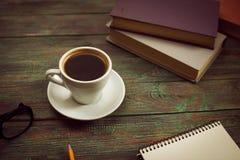 Ένα φλιτζάνι του καφέ στον εργασιακό χώρο σε έναν ξύλινο πίνακα Στοκ φωτογραφίες με δικαίωμα ελεύθερης χρήσης
