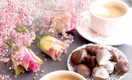 Ένα φλυτζάνι του ευώδους καφέ το πρωί και μια ανθοδέσμη των ρόδινων λουλουδιών Γλυκά σοκολάτας υπό μορφή κοχυλιών Κοχύλια στοκ φωτογραφία με δικαίωμα ελεύθερης χρήσης
