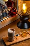 Ένα φλυτζάνι του εύγευστου καφέ στο υπόβαθρο ενός φωτεινού λαμπτήρα που στέκεται στο windowsill, δωμάτιο ντεκόρ του νέου έτους στοκ εικόνα με δικαίωμα ελεύθερης χρήσης