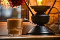 Ένα φλυτζάνι του εύγευστου καφέ στο υπόβαθρο ενός φωτεινού λαμπτήρα που στέκεται στο windowsill, δωμάτιο ντεκόρ του νέου έτους στοκ φωτογραφία με δικαίωμα ελεύθερης χρήσης