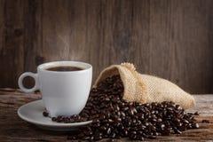 Ένα φλυτζάνι του καυτού καφέ σε έναν ξύλινο πίνακα με τα ψημένα φασόλια καφέ Στοκ εικόνα με δικαίωμα ελεύθερης χρήσης