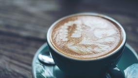 Ένα φλυτζάνι του καυτού καφέ latte με την τέχνη latte στο μπλε φλυτζάνι καφέ Στοκ εικόνες με δικαίωμα ελεύθερης χρήσης