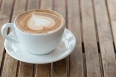 Ένα φλυτζάνι του καυτού καφέ latte, cappuccino ή espresso με τον αφρό γάλακτος στον αγροτικό πίνακα r στοκ εικόνες