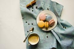 Ένα φλυτζάνι του καυτού cappuccino με την κανέλα και πολύχρωμα macaroons κέικ στοκ φωτογραφία με δικαίωμα ελεύθερης χρήσης