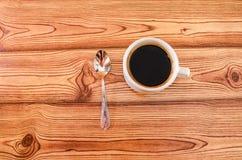 Ένα φλυτζάνι του μαύρου καφέ και ένα κουτάλι σε ένα ξύλινο υπόβαθρο E στοκ εικόνες