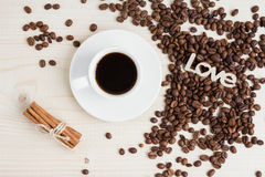 Ένα φλυτζάνι του μαύρου καφέ με τα φασόλια κανέλας και καφέ σε έναν ξύλινο πίνακα Στοκ Εικόνα