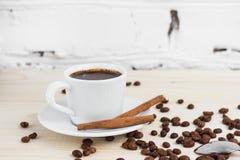 Ένα φλυτζάνι του μαύρου καφέ με τα φασόλια κανέλας και καφέ σε έναν ξύλινο πίνακα Στοκ εικόνες με δικαίωμα ελεύθερης χρήσης